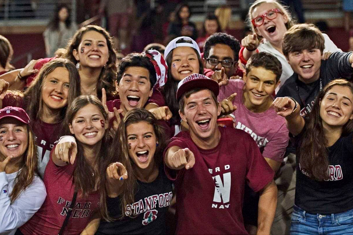 Group of Stanford students at a sporting event wearing Stanford gear and pointing to the camera.