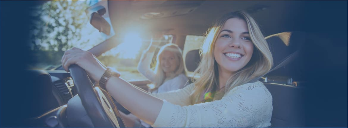 A woman driving a car with the sun coming in through the passenger window - OKFB insurance banner image