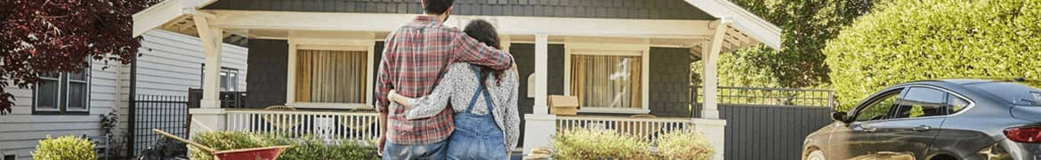 A couple standing in front of a  house thinking of home insurance, State Farm banner