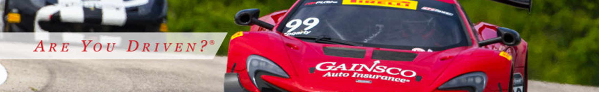 "Caption Text: ""Are you driven?"" Red racing car, with gainsco auto insurance decal on the hood. Gainsco banner image."