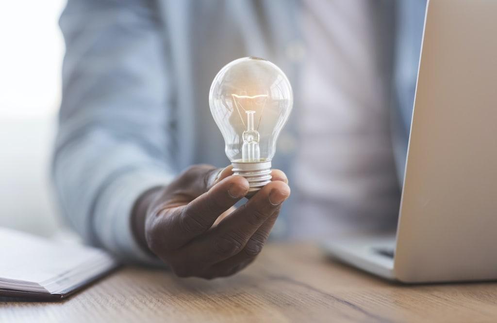 Black businessman holding illuminated light bulb in hand