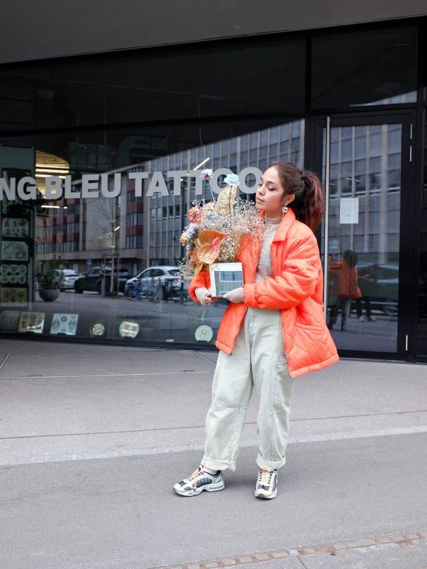 Jenni Tschugmell in Stüssy vor dem Sang Bleu Tattoo in Zürich mit ihren Blumen von Floral.TV