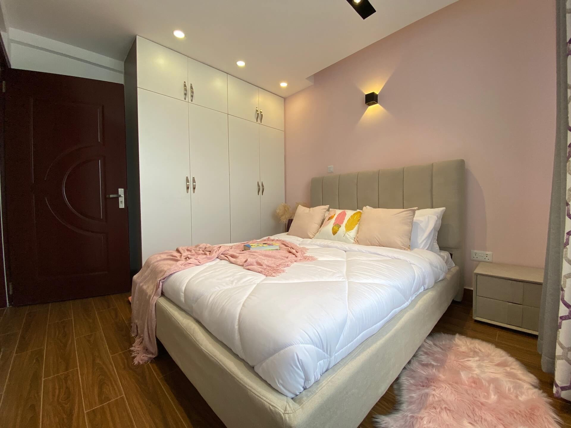 a fully furnished bedroom with pink walls