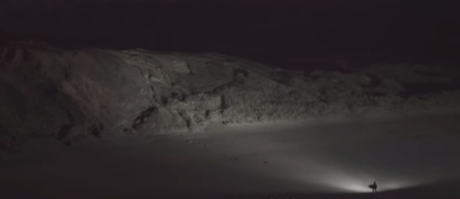 nightsurfer lighting a hill after a session
