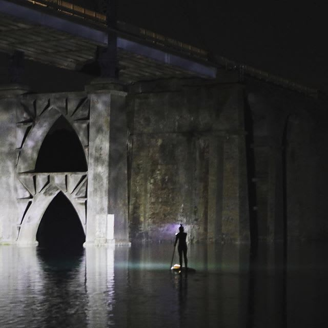 stand up paddle by night lighting a bridge