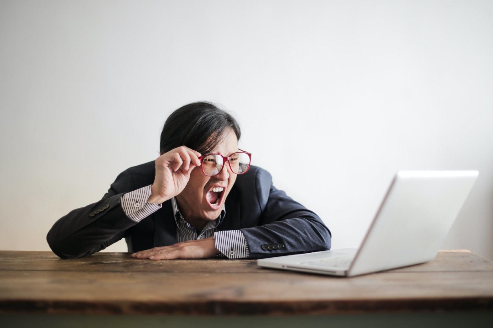 yelling formal man watching news on laptop