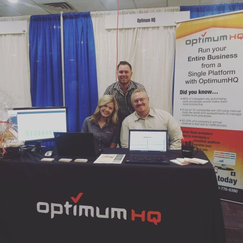 Audra, Kyle, and CEO Simon Chatfield sitting down at booth at trade show