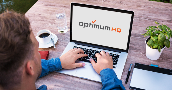 man on a computer with OptimumHQ logo on the screen