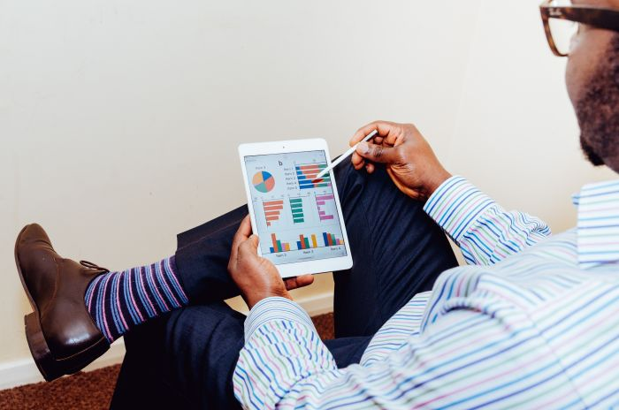businessman with ipad and business graphs