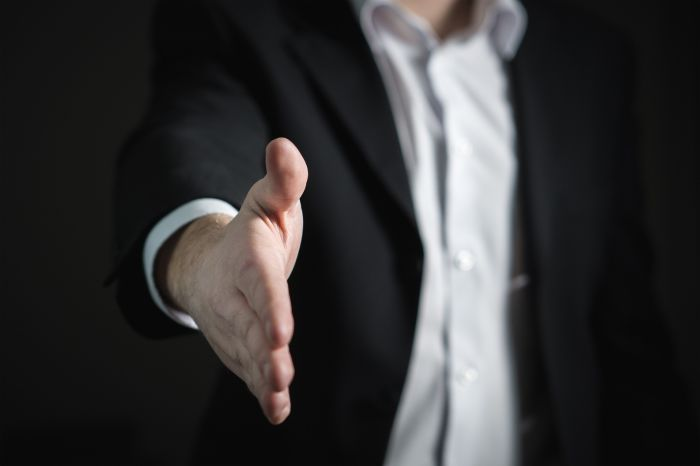 man in business suit extending his hand to shake