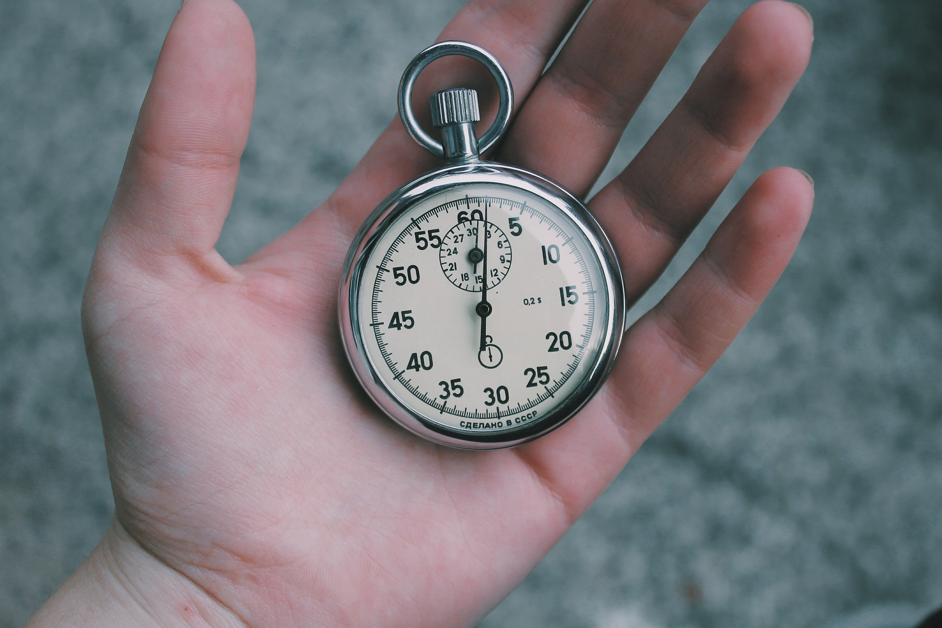 hand holding a pocket watch showing the time