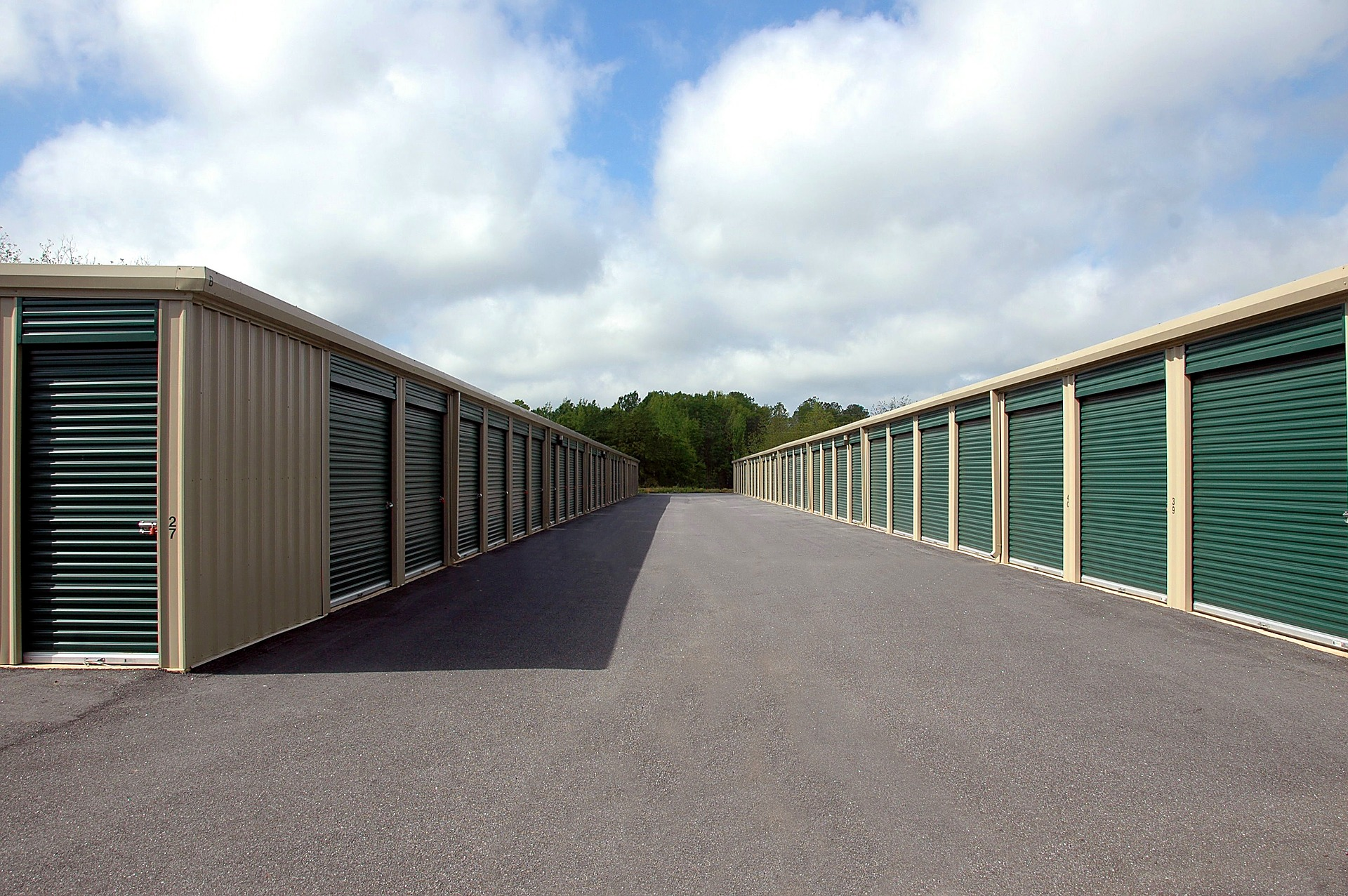 row of green and beige self storage units
