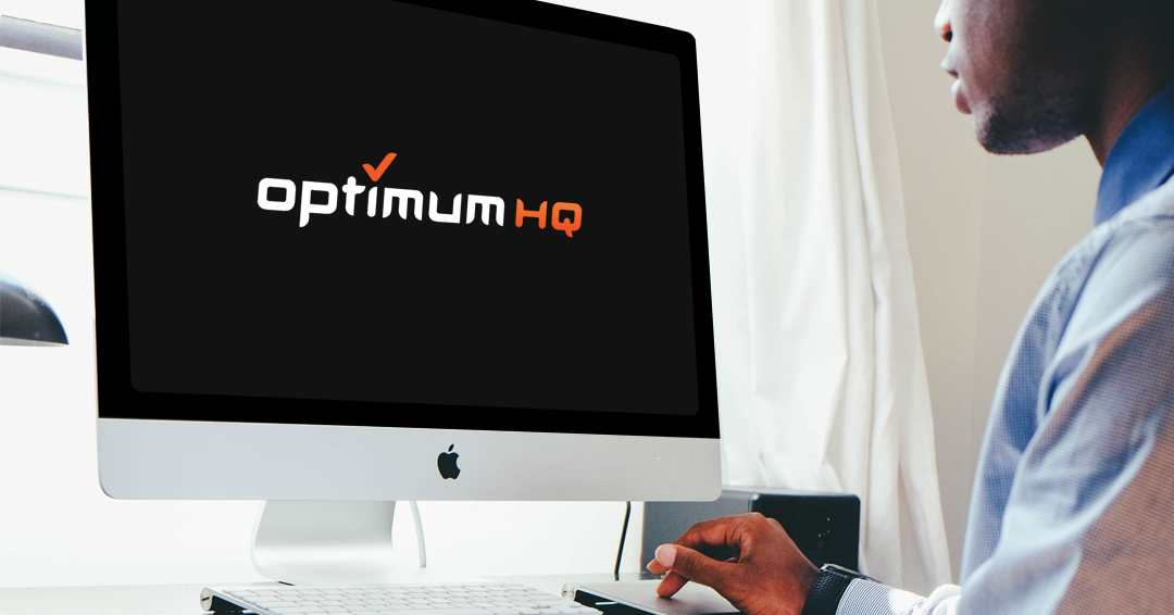 man using technology sitting at a computer screen with the OptimumHQ logo on it
