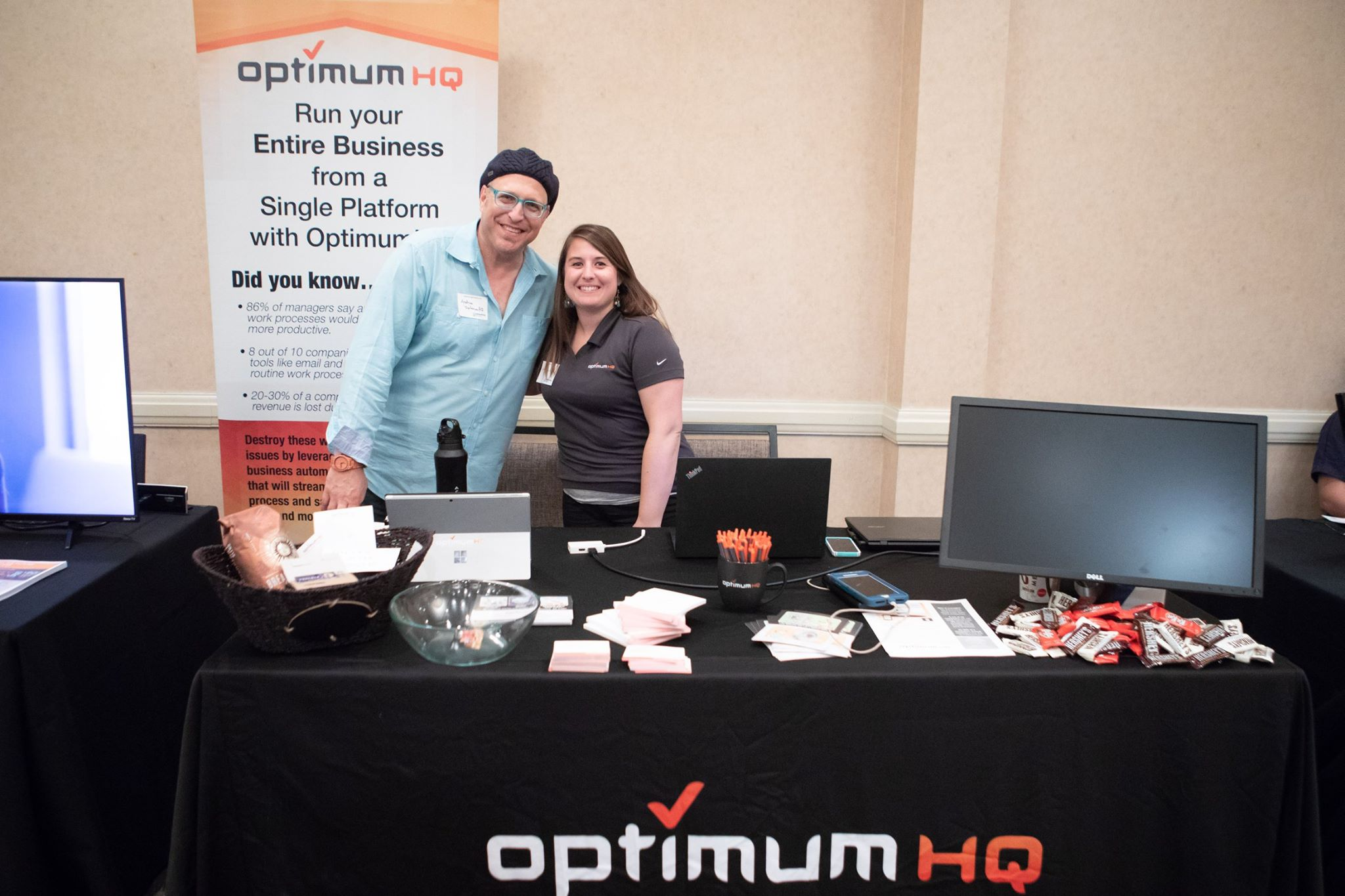 OptimumHQ employees Amanda and Andrew working a trade show booth