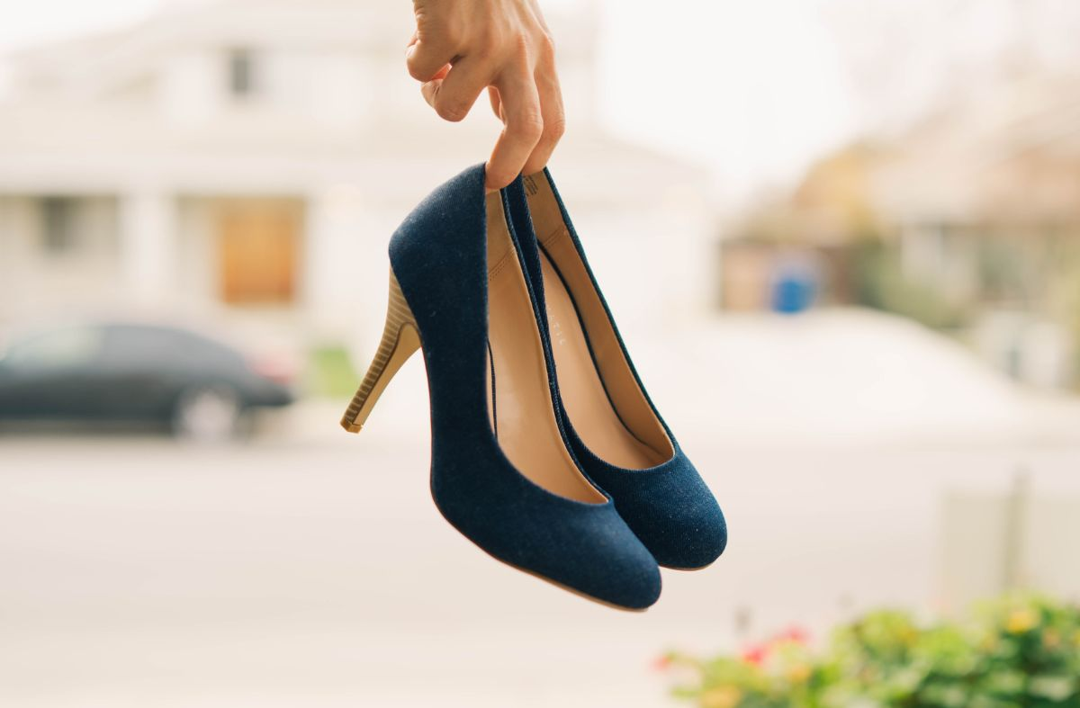 High-heeled shoes hanging off index and middle fingers.