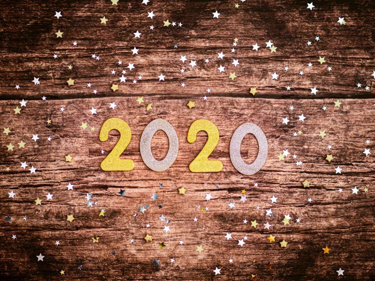 Paper or maybe felt '2020' and star confetti on a wood tabletop.