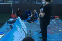 Young people painting a banner outside