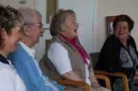 Image of four women sitting down, singing and laughing including a physiotherapist in uniform