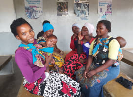 Five women with children waiting for their turn to vaccinate