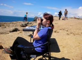 A young person sitting on a chair on a cliff, looking at the sea with binoculars