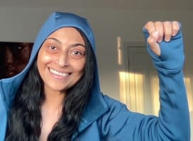 A person smiling in the camera, fist up celebrating a win