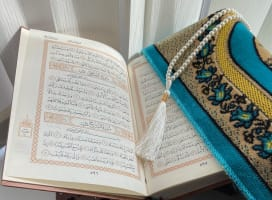 Two feet on a carpeted floor with a pair of white, fluffly socks neatly positioned next to the feet  The Quran, opened to show two pages