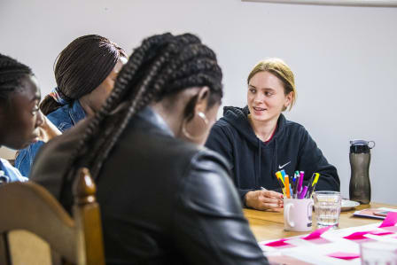 A young person smiling with other young people around a table. On the table there's a white page with bright pink post its on it and stationary scattered around.