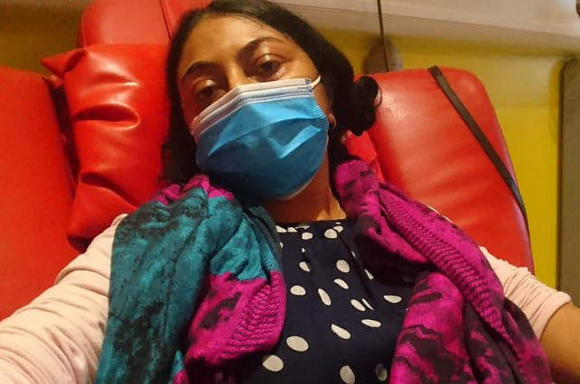 A person looking into the camera whilst sitting on a sofa chair receiving drip treatment