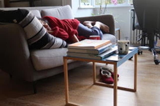 A person sleeping on the sofa under blankets, fatigued