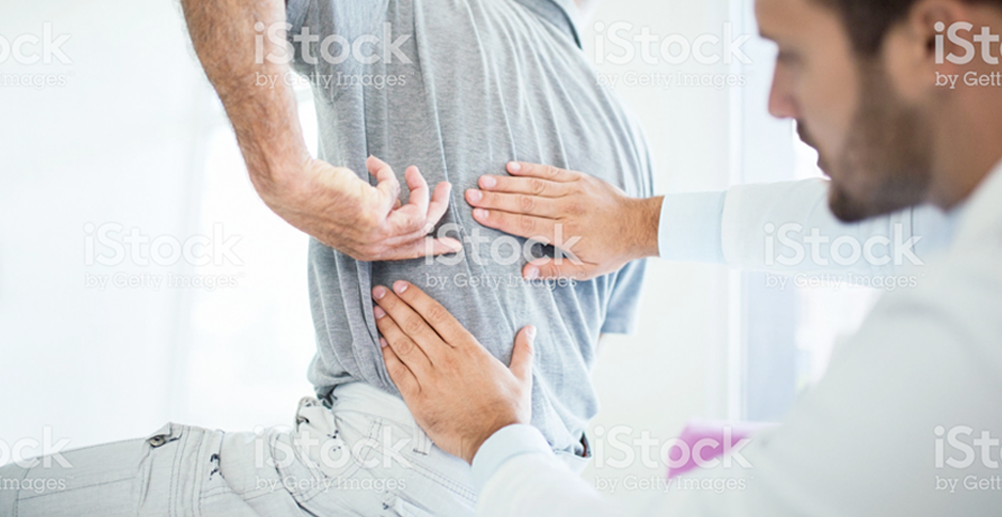patient pointing to sore back while chiropractor examines