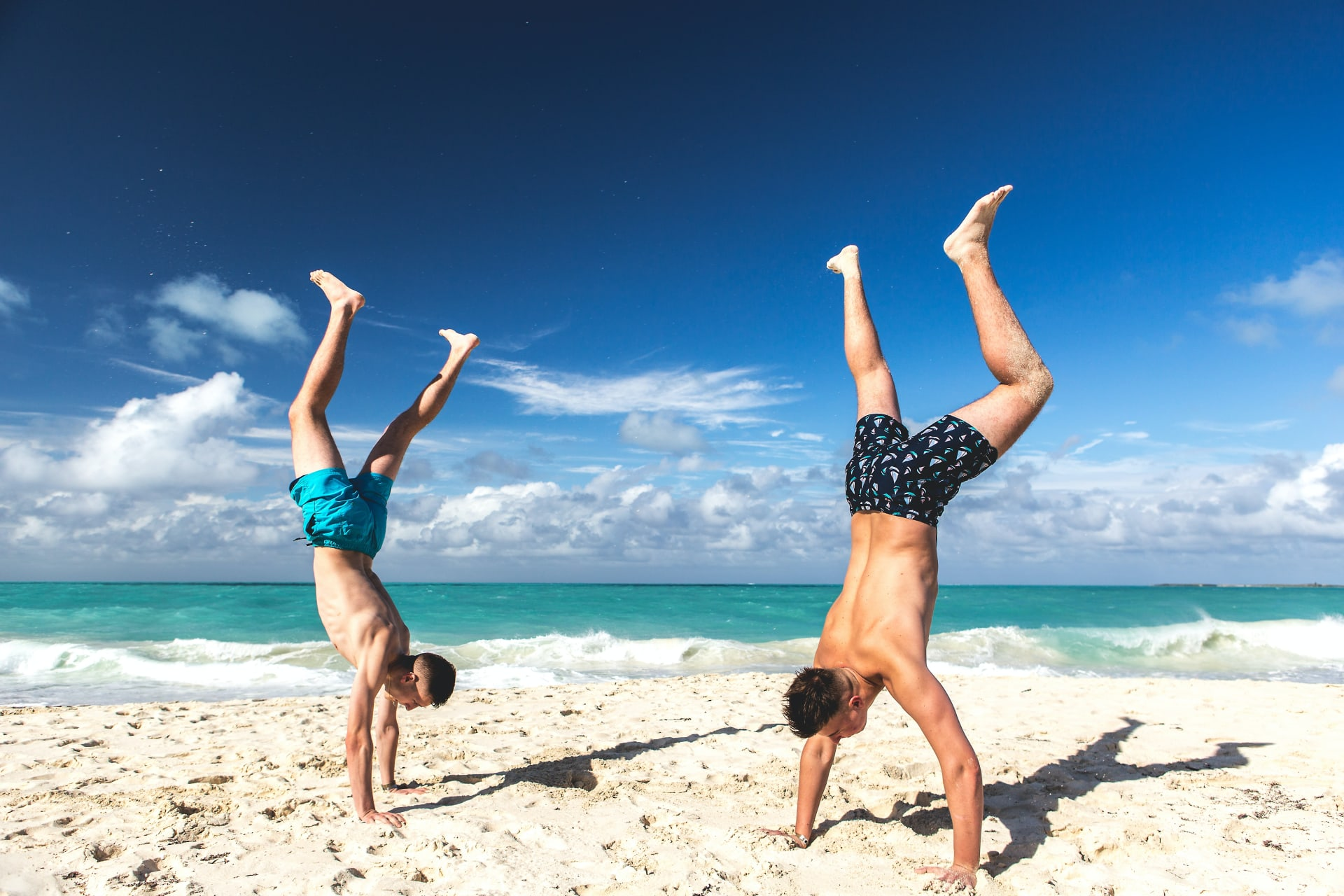Two guys standing on their hands on the beach