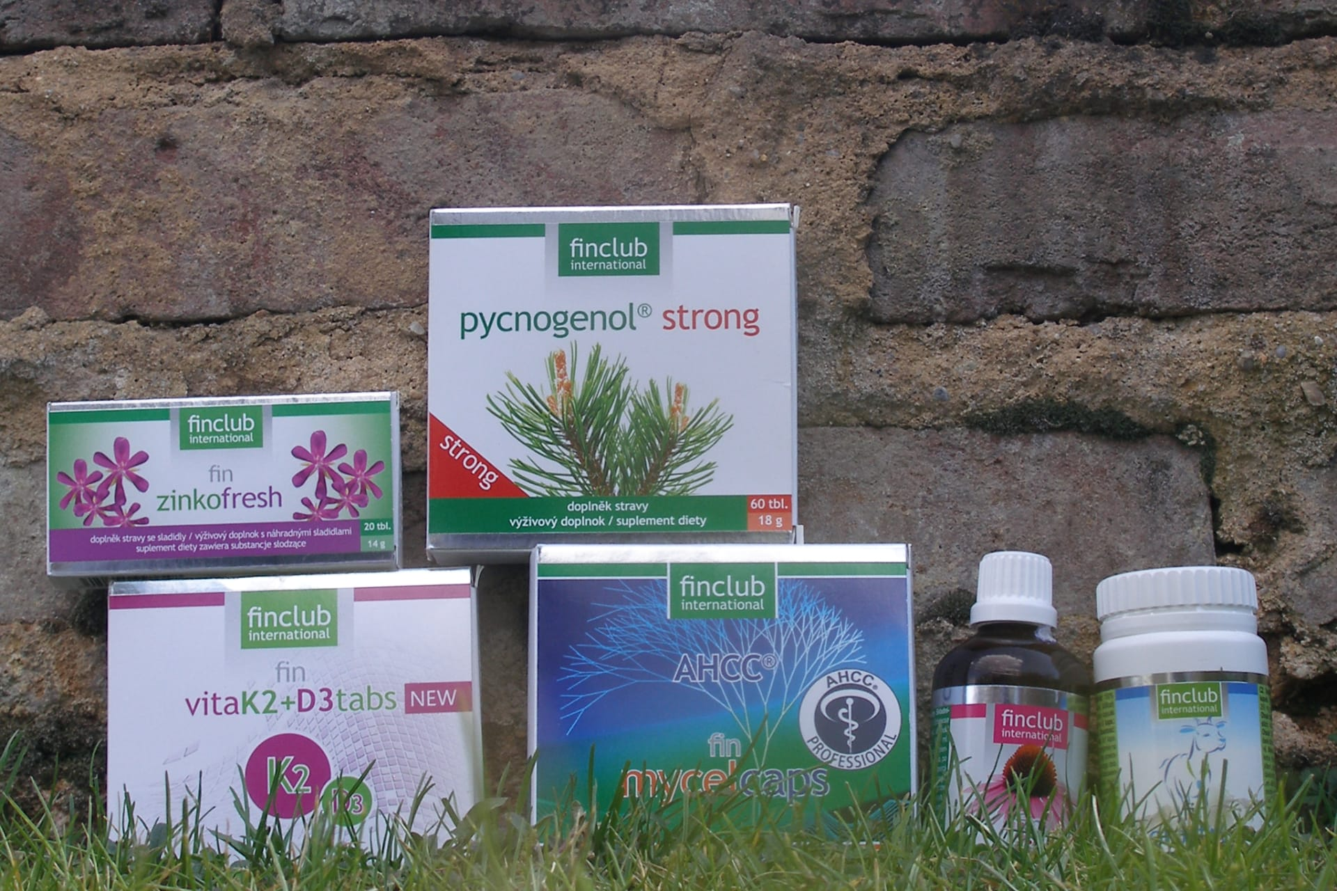 A group of dietary supplements by Finclub in the grass.