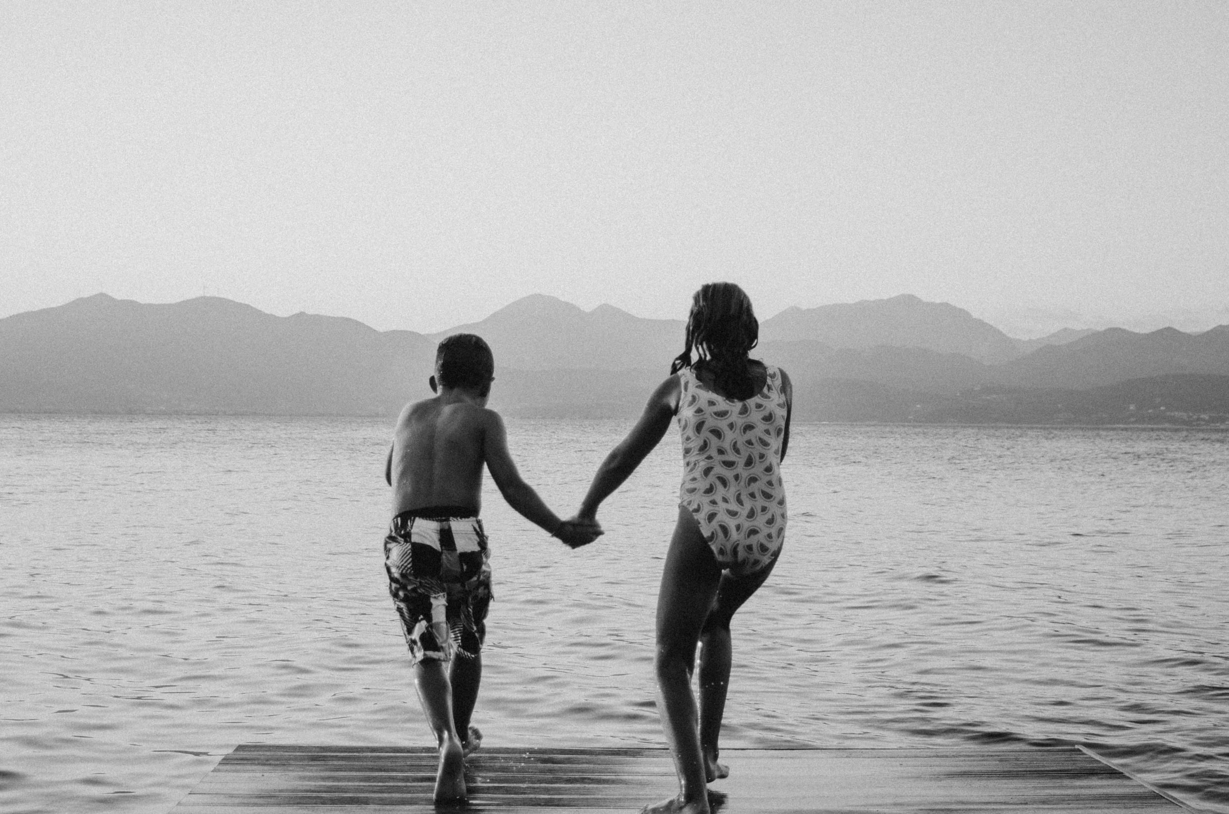 A boy and a girl hand in hand jumping into the water. Image by Constantinos Panagopoulos.