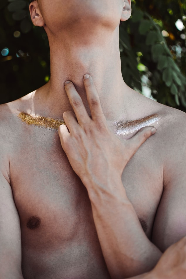 A man touching his neck. Photo by Taras Chemus.