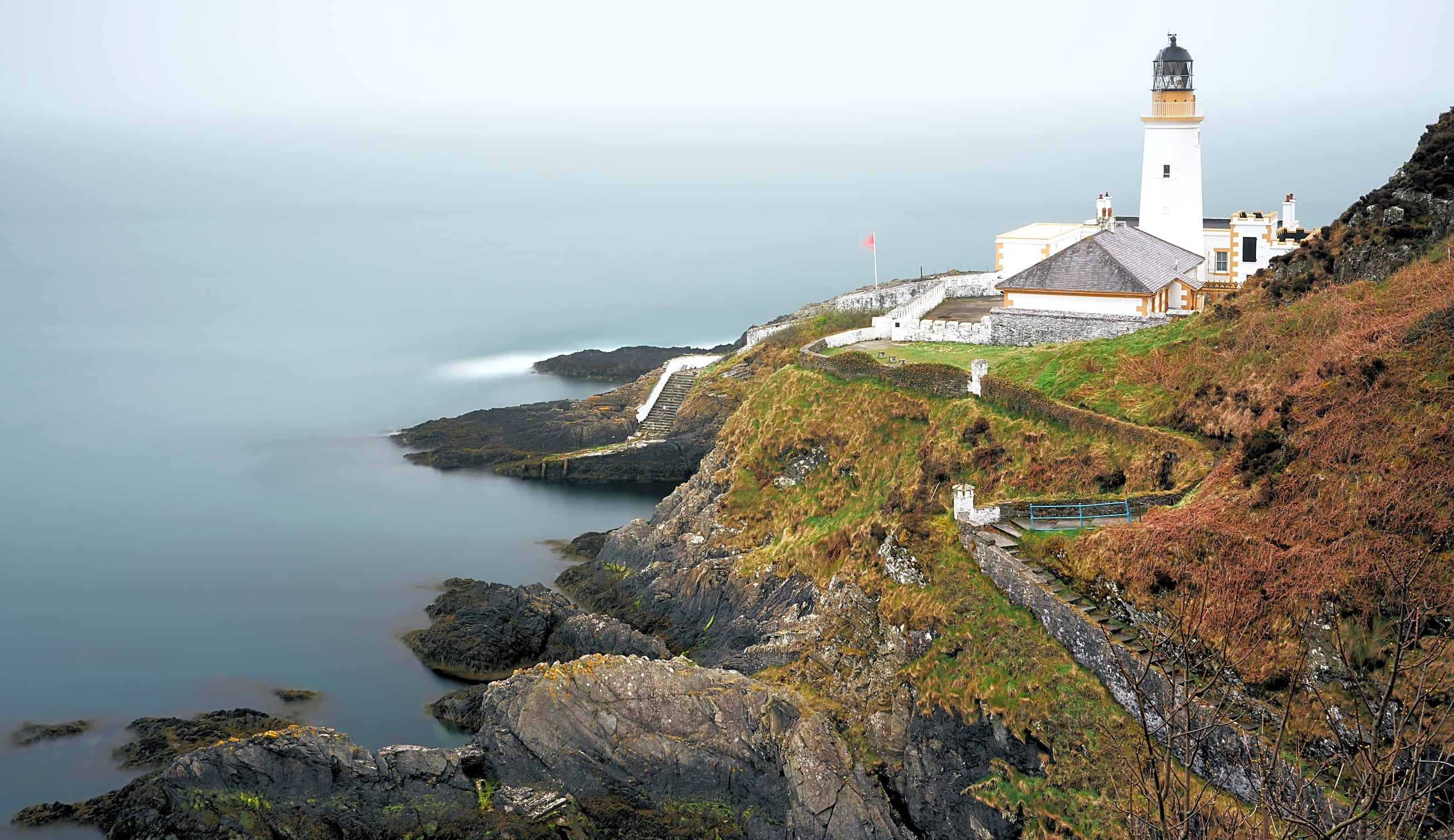 lighthouse on a rocky cliff on overcast, slightly foggy day