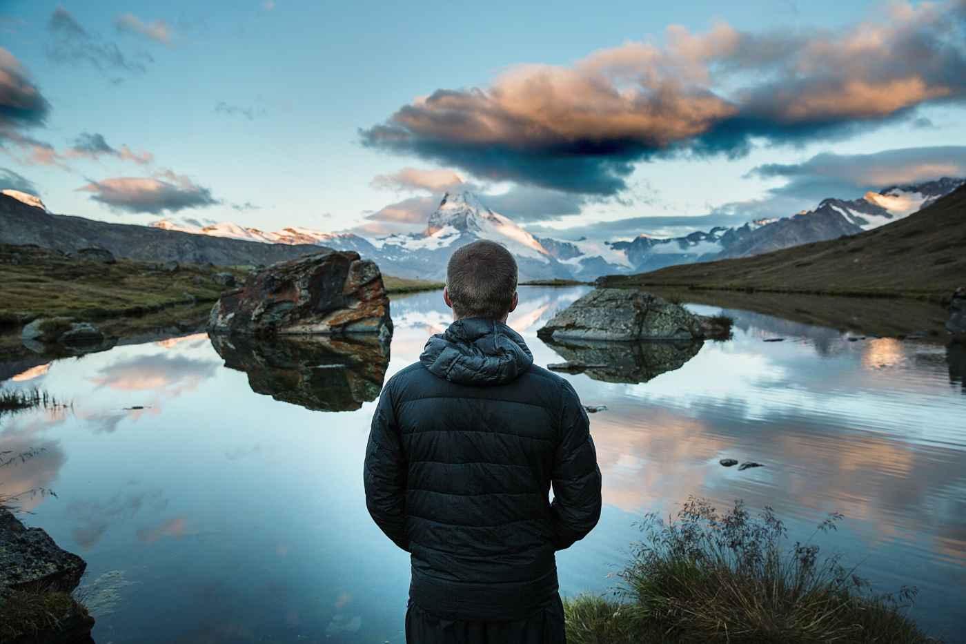 man looking across a lake to a mountain range