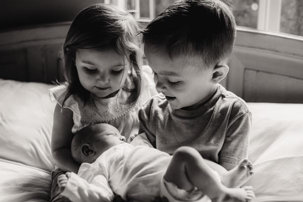 big brother and big sister hold their newborn baby brother in bed