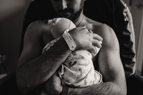 dad holds his newborn baby skin to skin