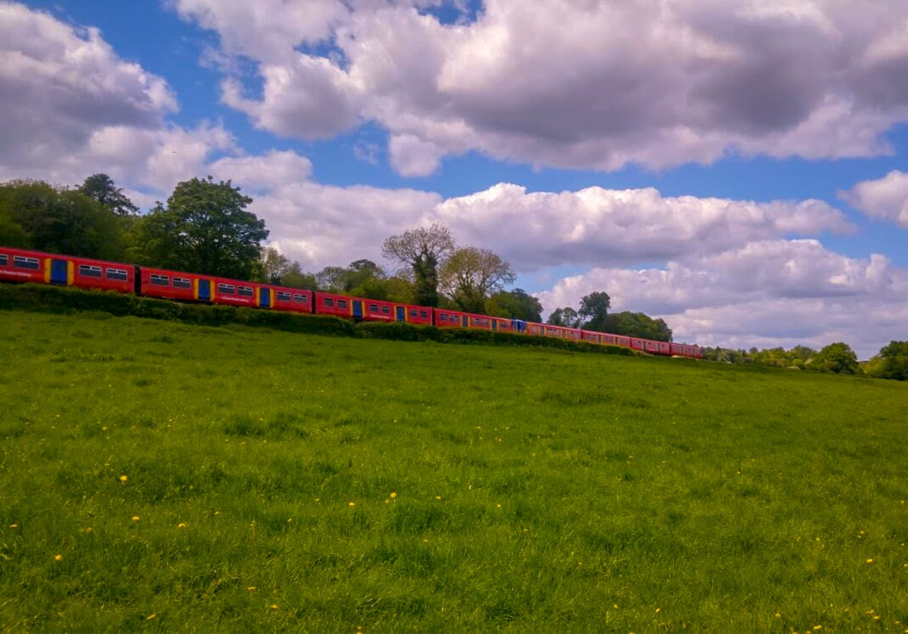 A Bright Red Train Racing Through the English Countryside