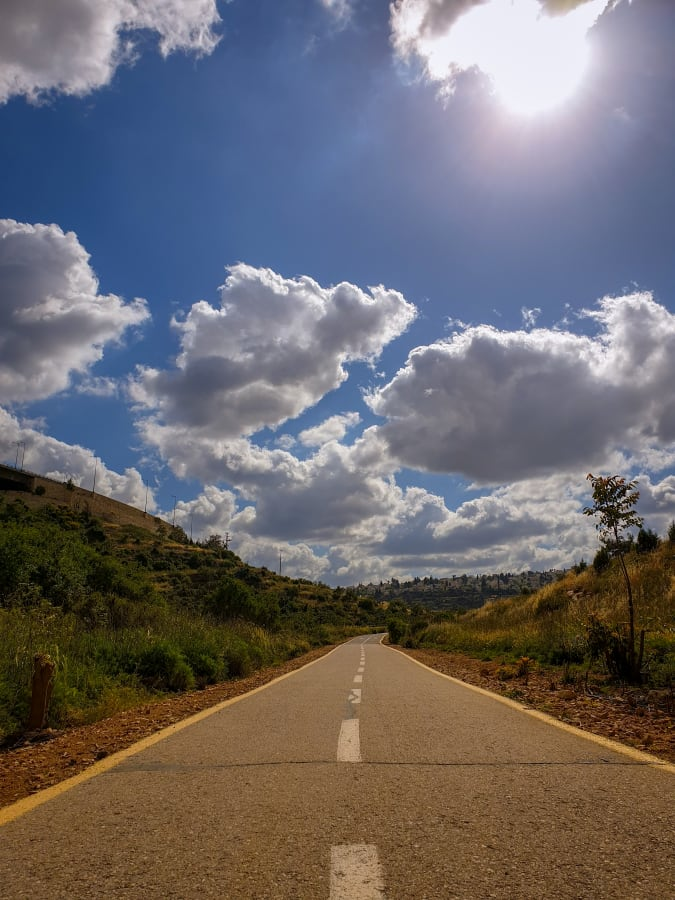 A Lovely Road Under a Blue Sky With Big Fluffy White Clouds