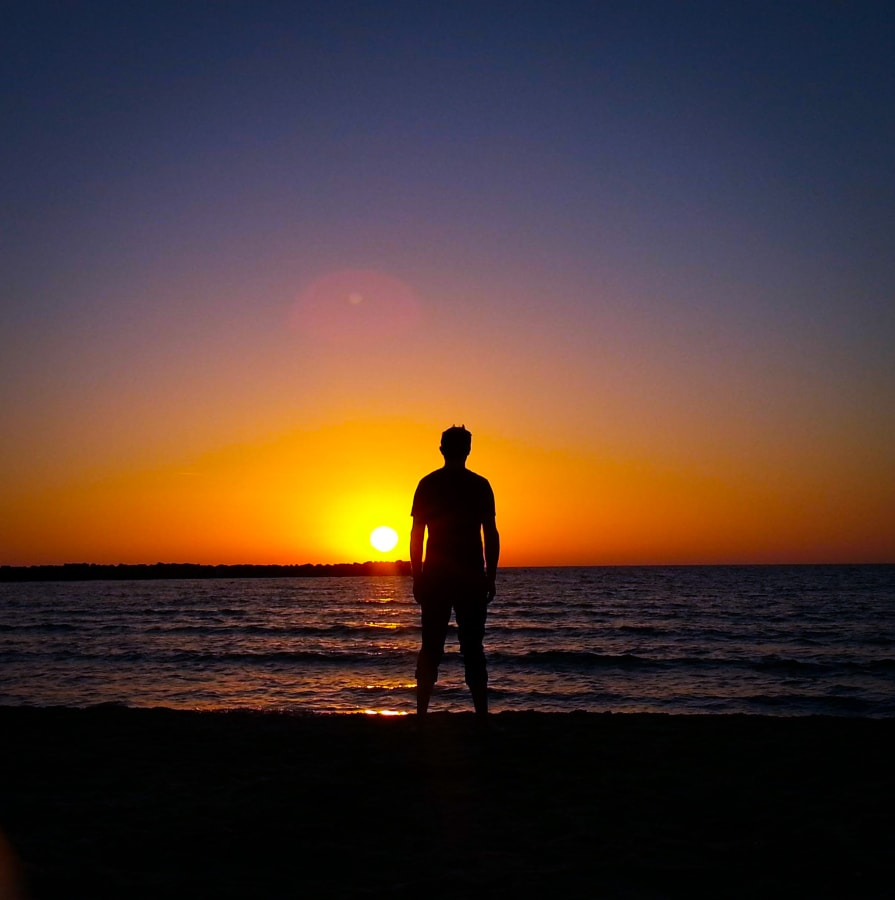 Silhouette of a Man Staring Off Into a Sunset at the Beach