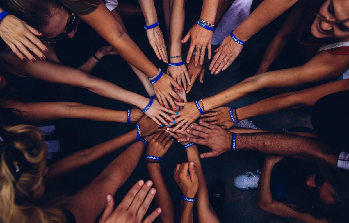 Viele Hände liegen aufeinander und an jedem Handgelenk ist ein blaues Armband zum Zeichen der Zugehörigkeit