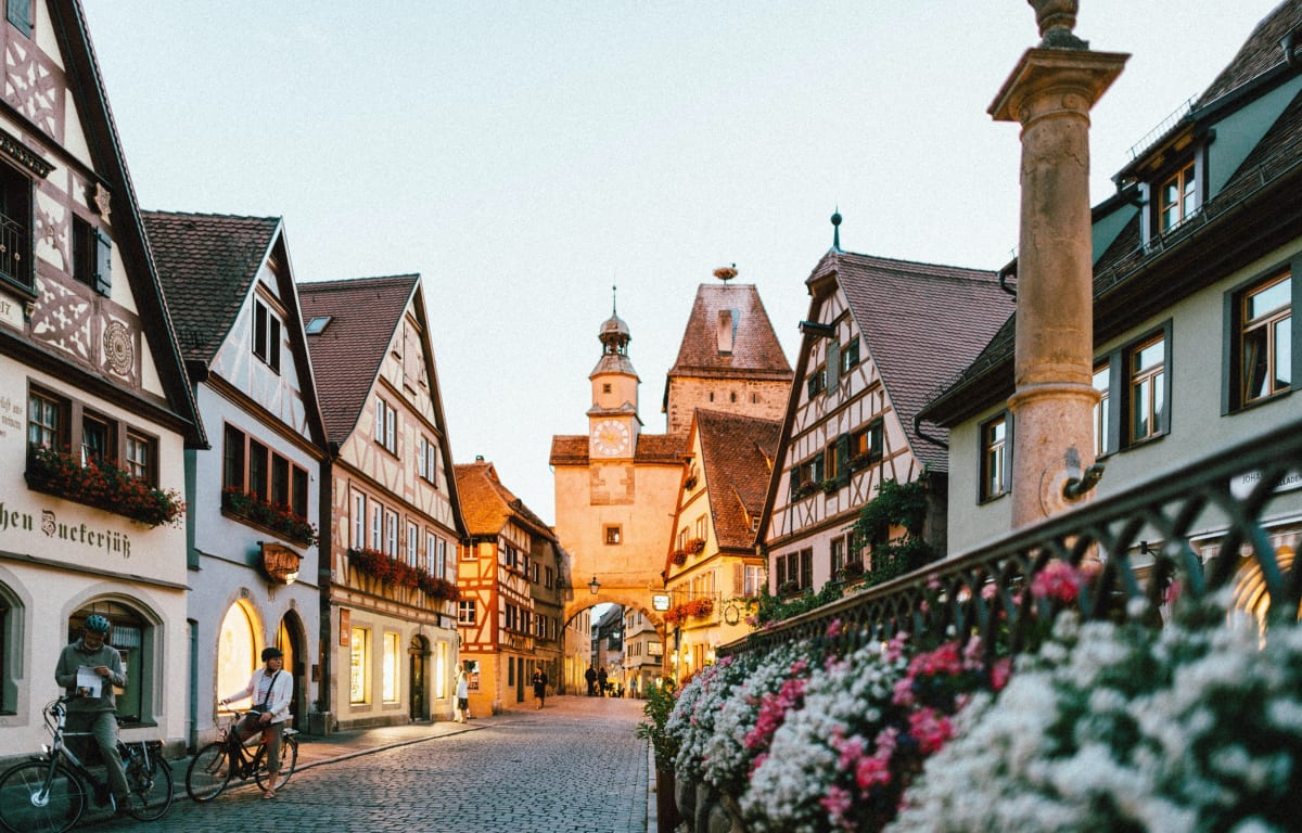 Rothenburg ob der Tauber ist ein malerisches Städtchen in Bayern. Zu sehen sind alte Fachwerkhäuser und spitze Kirchtürme im Sonnenuntergang und ein alter Brunnen mit weißen und pinken Blumen.