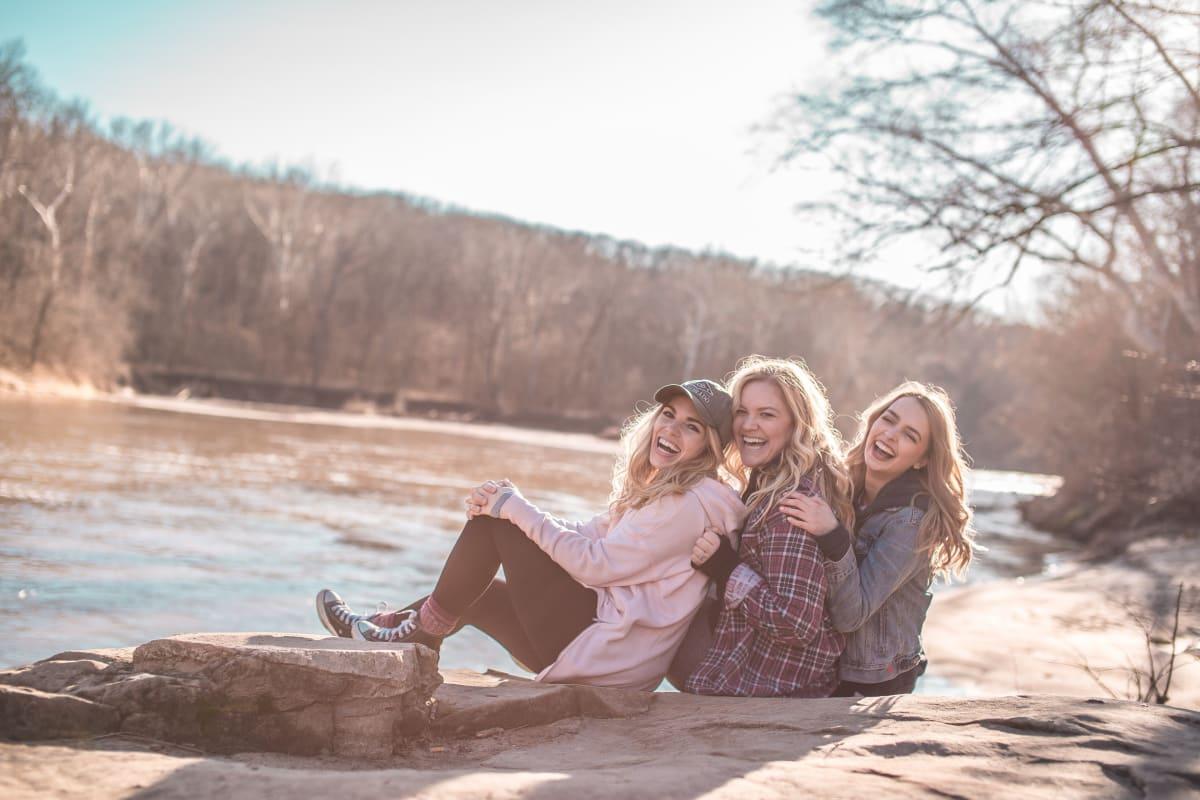 Drei blonde junge Frauen lachen in die Kamera und sitzen an einem Fluss und umarmen sich