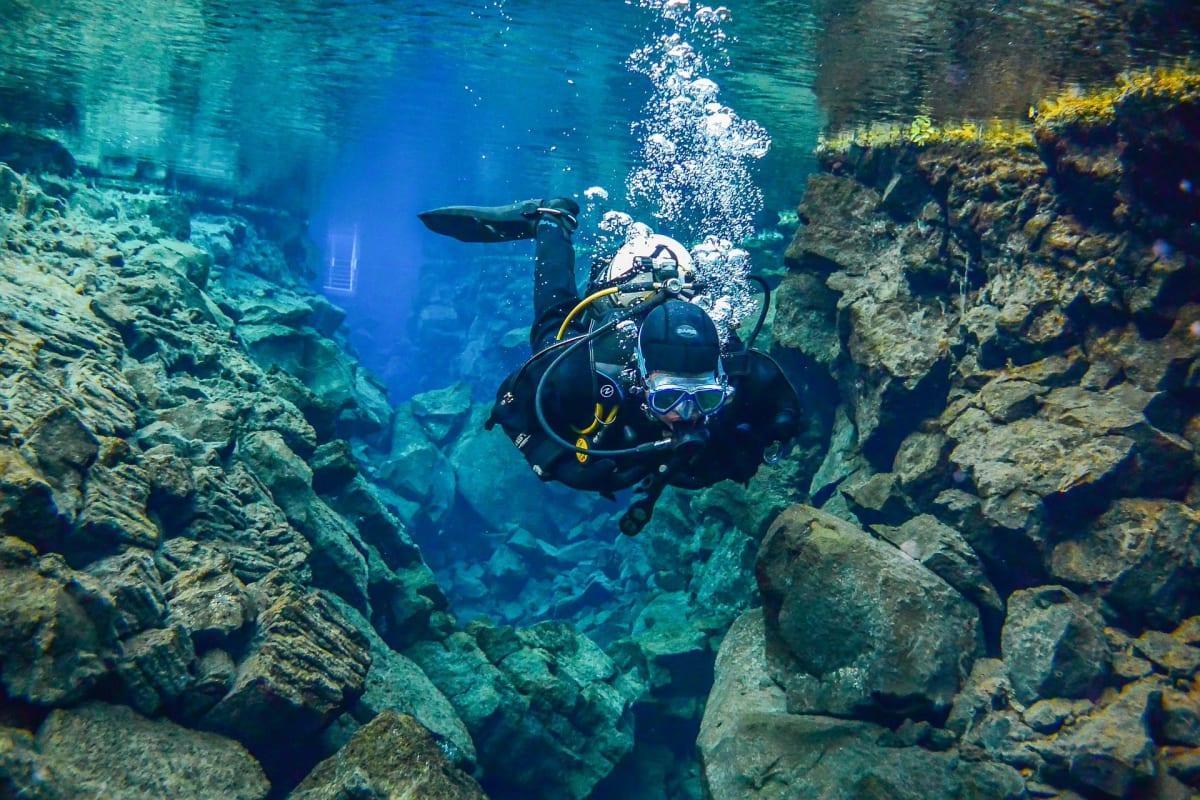Taucher im schwarzen Neoprenanzug in der Silfra Spalte in Island, im saubersten Wasser der Welt.