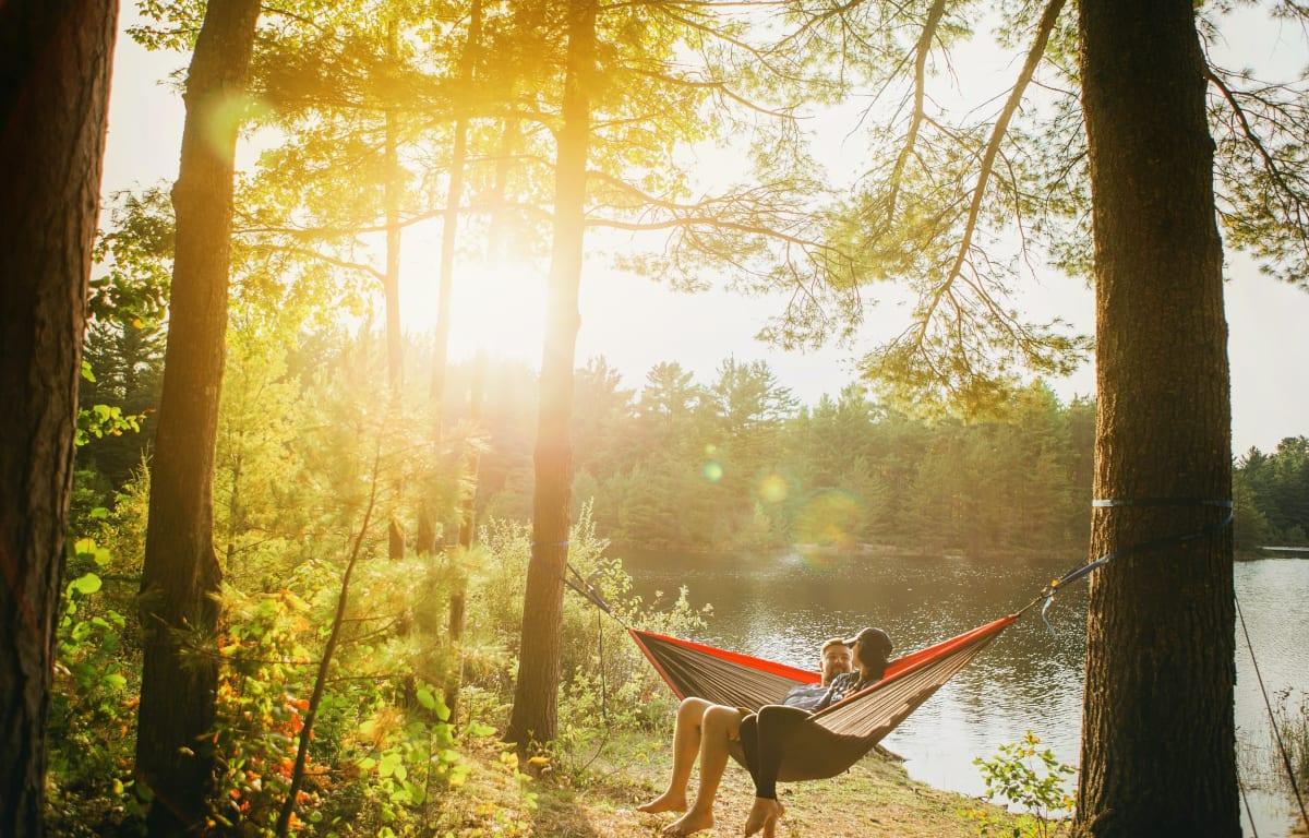 Pärchen in einer Hängematte an einem See in der Nähe eines Campingplatzes