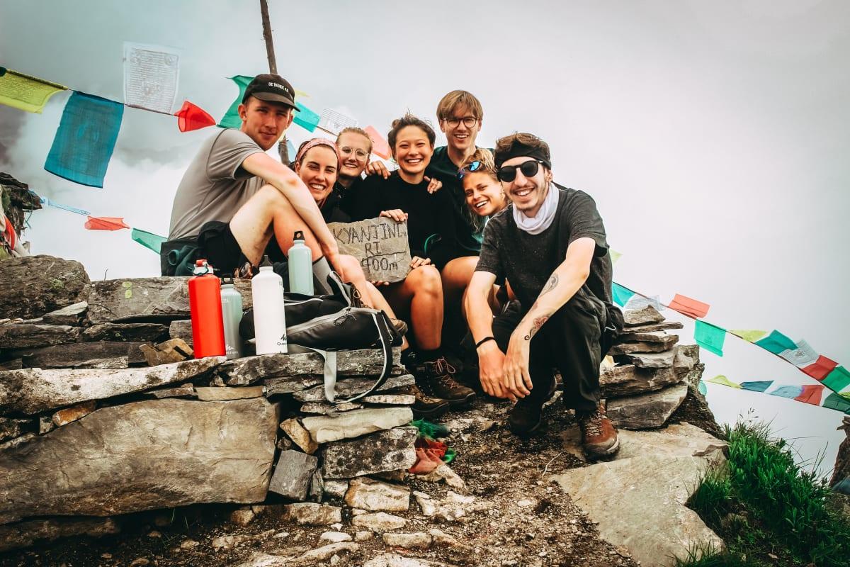 Lächelnde Reisepartner auf einem Felsvorsprung in Nepal mit Gebetsfahnen im Hintergrund