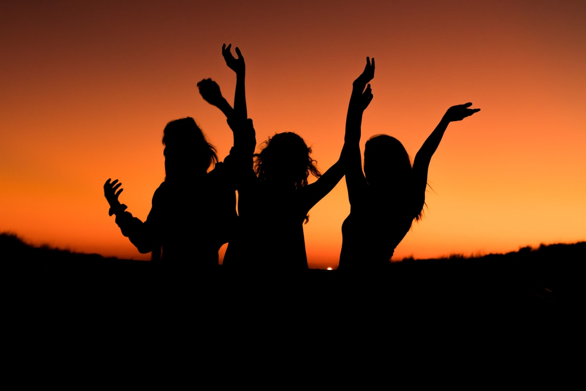three girls dancing in light of the sunset
