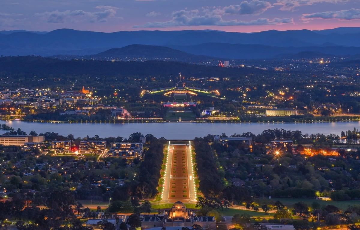 Canberra, die Hauptstadt von Australien, fotografiert bei Nacht und den Australischen Alpen im Hintergrund