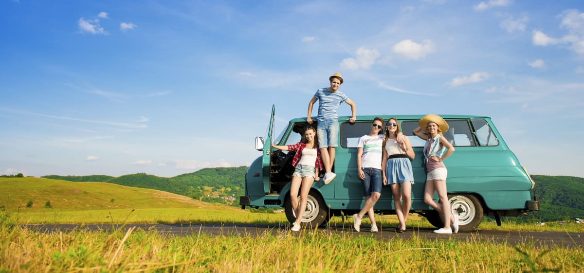 Junge Gruppenreise Reisegruppe vor einem Camper Van im Sommer